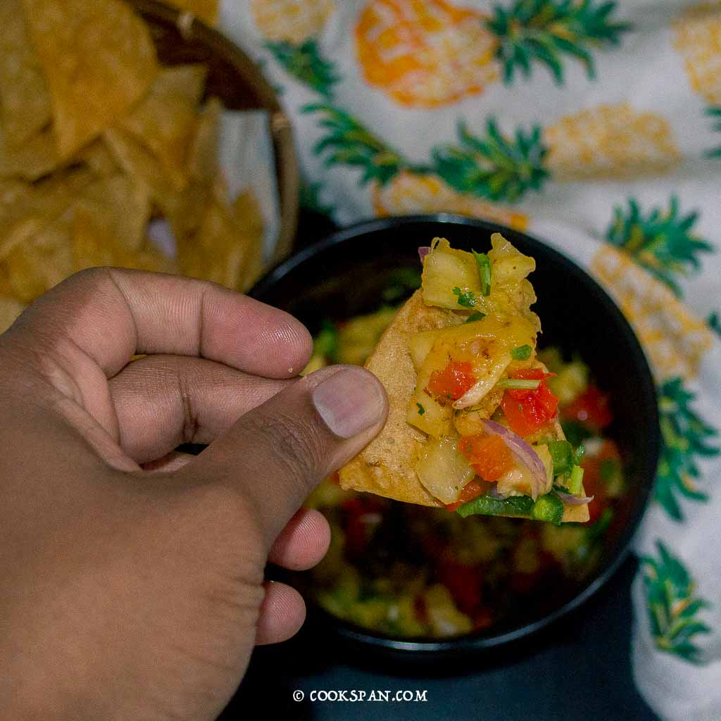 Tortilla chips with a generous bite of salsa